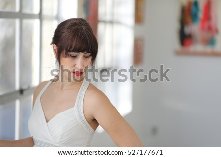 Photo of an adult woman with brown hair and eyes. She is in a white dress and visiting an art gallery.   (The paintings in this photo have been digitally altered and don't look like the originals).