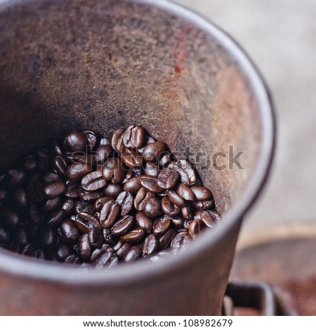 Photo of an antique coffee grinder with coffee beans