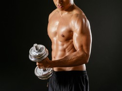 Photo of an Asian male exercising with dumbbells and doing bicep curls over dark background.