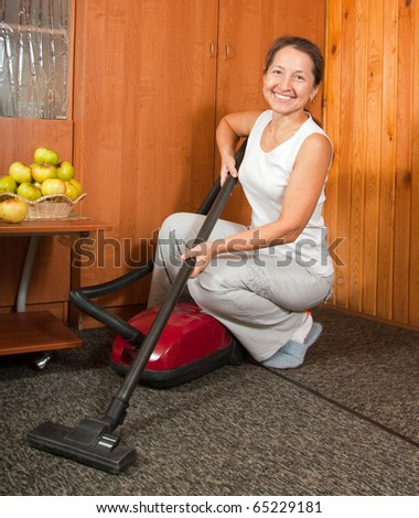 Photo of an attractive senior woman vacuuming her living room.