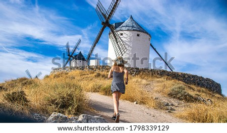 Photo of an attractive woman standing next to some beautiful and historic windmills located in Consuegra, Toledo, Spain during a sunny day of summer in a natural place.  Foto stock ©