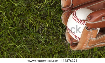 Photo of an Baseball ball and glove on green grass. Outdoor scene
