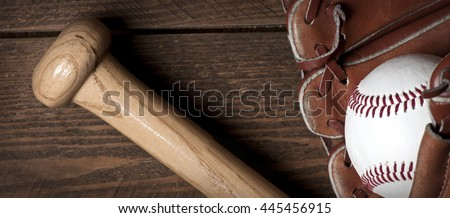 Photo of an Baseball ball, glove and bat on wooden table. Studio shot