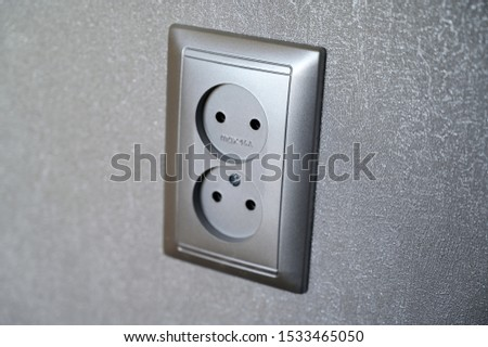Photo of an electrical outlet in a gray wall in a room. Industry, electrics.