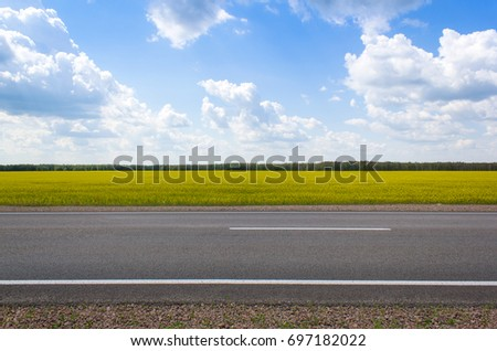 Shutterstock Photo of an empty summer road. On the road there are no cars, the weather is cloudy