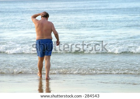 Photo of an obese man walking into the water.