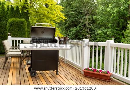 Photo of an open barbecue cooker with cold beer in bucket on cedar wooden patio. Table and colorful trees in background.  #281361203