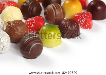 Photo of assorted truffles, pralines, and liqueur filled chocolates on white background.