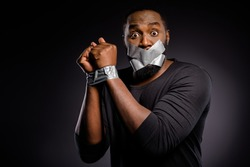 Photo of astonished afro american guy restrain arrested police hand adhesive taped lips close cover no talking speaking taboo isolated over black color background