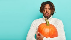 Photo of astonished black man holds big orange pumpkin, scared by something, has specific hairstyle, surprised with rich seasonal harvest, wears white sweater. People and Halloween preparation concept