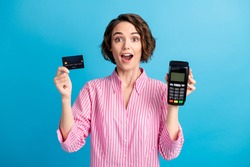Photo of astonished lady hold pos terminal show credit card wear formal white pink shirt isolated on blue color background