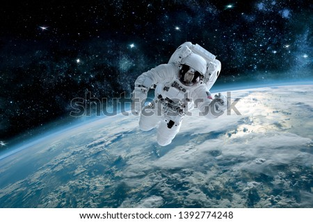 Photo of astronaut in space, in background planet earth. Elements of this image furnished by NASA. #1392774248