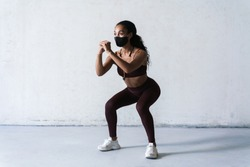 Photo of athletic african american woman in face mask doing exercise while working out indoors
