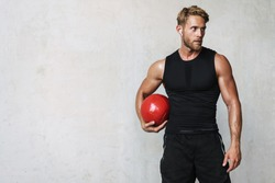 Photo of athletic young sportsman in earphones working out with medicine ball isolated over white wall