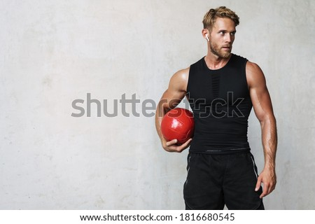 Photo of athletic young sportsman in earphones working out with medicine ball isolated over white wall Foto stock ©