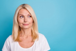 Photo of attractive aged lady good mood look side empty space wear casual white t-shirt isolated blue color background