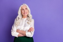 Photo of attractive aged white haired lady smiling good mood arms crossed look up empty space dreamy wear white blouse green long midi skirt isolated pastel purple color background
