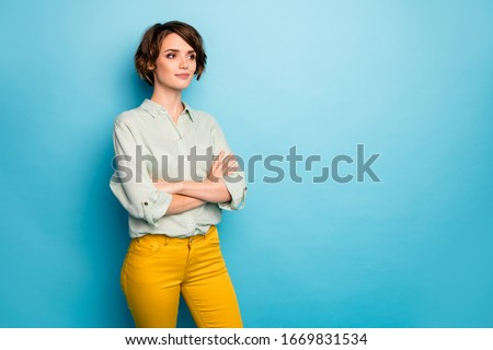 Photo of attractive business lady short hairstyle not smiling serious reliable person arms crossed wear casual green shirt yellow trousers isolated blue color background
