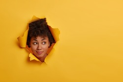 Photo of attractive curly African American woman looks with curious expression aside, notices something interesting, has natural beauty, isolated over yellow background in paper hole, has fun indoor