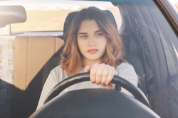 Photo of attractive female driver sits in car, teaches to drive, being inexperienced, has thoughtful expression. Woman in transport, stuck in traffic jam, thinks about something during long journey