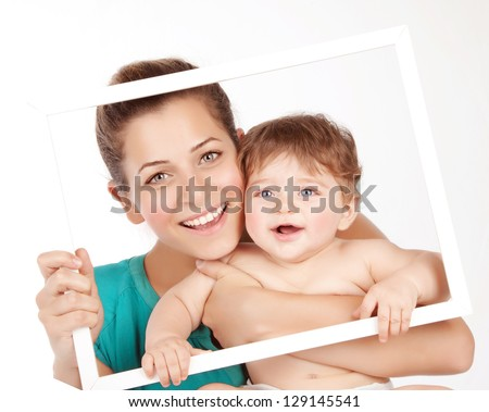 Photo of attractive female holding in hands cute baby boy, closeup portrait of young mother hug her little son, white frame decorations, studio shot, happy family, child care and love concept