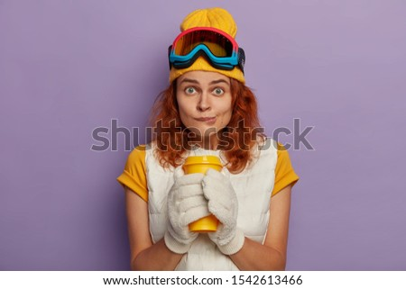 Photo of attractive female model has ginger hair, bites lips and holds takeaway cup with both hands, looks directly at camera wears yellow t shirt with vest reaches top of mountain likes snowboarding