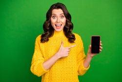 Photo of attractive funky lady hold telephone direct finger device advert new smart phone model cool modern interface wear yellow knitted jumper isolated green color background