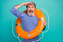 Photo of attractive funky shocked aged seaman open mouth security saving life buoy look far away see earth land wear striped sailor shirt isolated teal color background