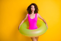 Photo of attractive funny terrified lady relax rest resort prepare swim big round circle afraid step into water frightened face wear pink swimsuit isolated vivid yellow color background