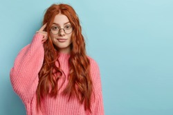 Photo of attractive ginger pupil with long wavy hair, tries to memorize something, keeps fore finger on temple, reminds information for exam, wears spectacles and jumper, stands over blue wall