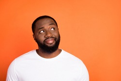 Photo of attractive happy young afro american man look empty space dream isolated on orange color background