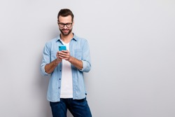Photo of attractive macho guy perfect appearance neat hairstyle easy-going person holding browsing telephone wear specs casual denim outfit isolated grey color background