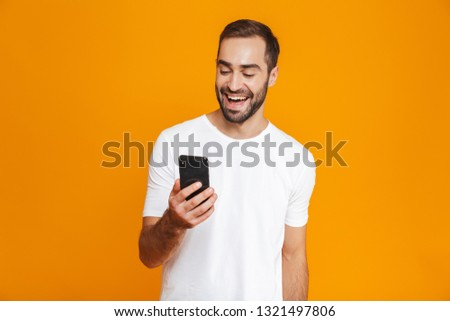 Photo of attractive man 30s in casual wear smiling and holding smartphone isolated over yellow background