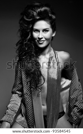 Photo of attractive smiling beautiful woman with magnificent hair and sweet smile posing on dark background