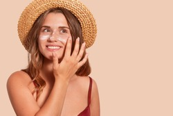 Photo of attractive smiling woman with long hair, has happy facial expression, applaying sunscreen, wearing straw hat, wanting to tan, isolated on beige wall. Summertime, vacation, sunscreen concept.