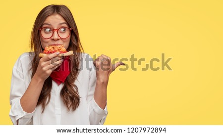 Photo of attractive woman eats slice of pizza, points aside with thumb, dressed in fashionable clothes, shows where pizzeria is, isolated over yellow background. Pretty girl has snack with fastfood
