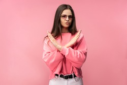 Photo of attractive young woman in glasses, not allow to do something, dislike and disagree. Wears casual pink t-shirt white pants isolated pink color background
