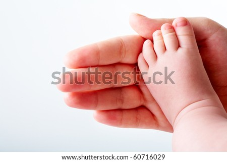 Photo of baby foot on his mother?s palm in isolation