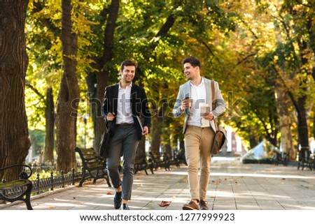 Photo of bearded businessmen in suits walking outdoor through green park with takeaway coffee and laptop during sunny day