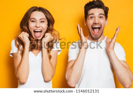 Photo of beautiful admired couple man and woman in basic clothing screaming in surprise or delight and touching cheeks isolated over yellow background