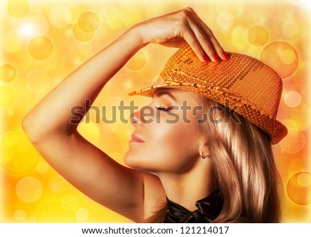 Photo of beautiful blond woman wearing stylish golden shiny hat, rear view of gorgeous female with closed eyes isolated on yellow blur background, disco club, night life, New Year party, Christmas eve