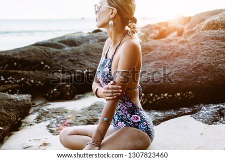 Photo of beautiful boho styled model wearing ethnic swimwear and silver bohemian jewelery on the beach in sunset