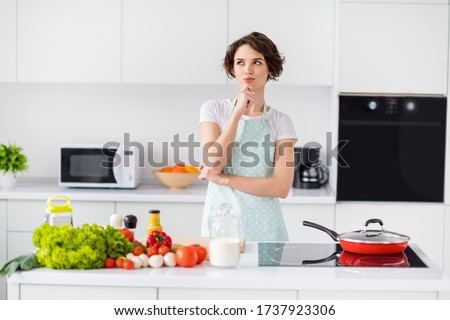 Photo of beautiful housewife holding arm on chin remind recipe minded enjoy weekend morning cooking tasty dinner family meeting wear apron t-shirt stand modern kitchen indoors