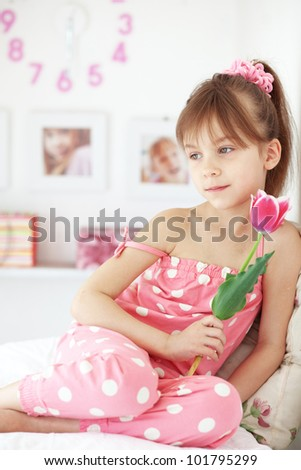 Photo of beautiful kid girl with flower at home