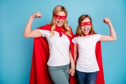 Photo of beautiful mom lady little daughter spend time together carnival super hero costumes showing strength muscles wear s-shirts red coat masks isolated blue color background