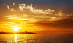 Photo of beautiful orange sunset on the sea, silhouette of lebanese city in sunrise on seashore, peaceful landscape, sun down on town on coast, warm weather, romantic vacation, holiday concept