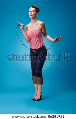 Photo of beautiful pin-up girl with tattoos and tattoo machine tattooing herself and looking at the camera - stock photo