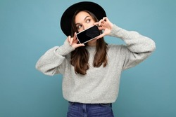 Photo of Beautiful positive woman person wearing black hat and grey sweater holding mobilephone showing smartphone isolated on background lookingto the side
