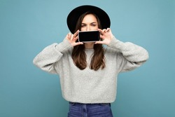 Photo of Beautiful positive young female person wearing black hat and grey sweater holding mobilephone showing smartphone isolated on background looking at camera