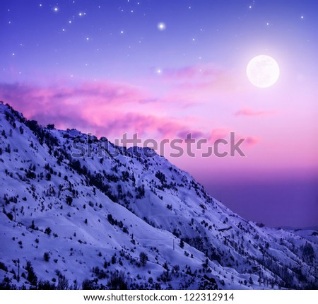 Photo of beautiful snowy mountains on purple sunset background, Faraya mountain in Lebanon covered with white snow, wintertime cold weather, moonlight in dark night, winter holidays concept